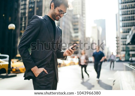 Cheerful male trader dressed in elegant suit laughing while reading good business news on internet website on smartphone.Happy businessman received notification of high financial balance on cellular #1043966380