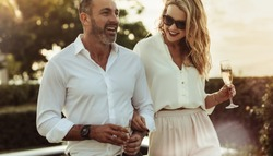 Cheerful man and woman with a drink outdoors. Wealthy couple together with a glass of wine.