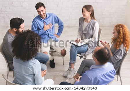 Cheerful man appreciates support of people at rehab group meeting, empty space