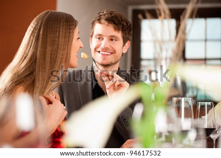Cheerful man feeding his girlfriend at hotel on a special occasion
