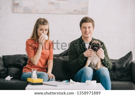 cheerful man holding cute pug while sitting on sofa near sneezing woman allergic to dog