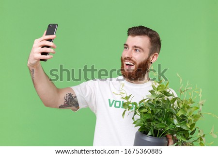Photo of Cheerful man in white volunteer t-shirt isolated on pastel green background. Voluntary free work assistance help charity grace teamwork concept. Doing selfie shot on mobile phone hold green flowerpot