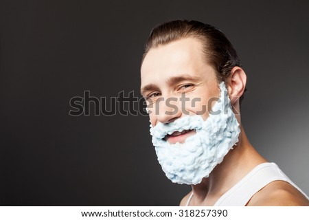 Cheerful man is shaving his beard with joy. He is applying shaving foam on his face. The man is standing and smiling. Isolated on grey background and copy space in left side