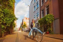 Cheerful man on bike riding along narrow streets in Amsterdam