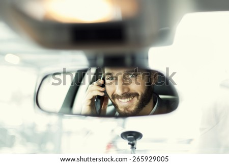 Cheerful man on mobile phone in the car. Reflection in the mirror