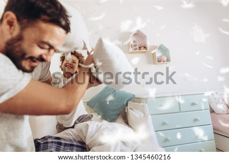 Cheerful man pillow fighting with son sitting on bed at home. Father and son having fun playing with pillows with feathers flying around.
