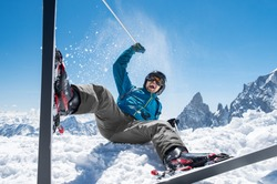 Cheerful man playing with snow while sit with ski. Happy smiling skier enjoying sitting on snow with ski equipment. Man having fun on snowy mountain.