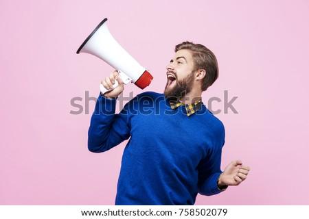 Cheerful man shouting into megaphone #758502079