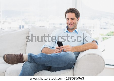 Cheerful man sitting on the couch using his smartphone at home in the living room #189095963