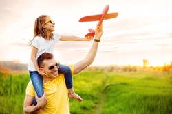 Cheerful man smiling and carrying excited girl on shoulders while playing with red aircraft together against cloudy sky on sunny summer day