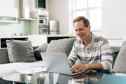 cheerful man smiling while using laptop near credit card in living room