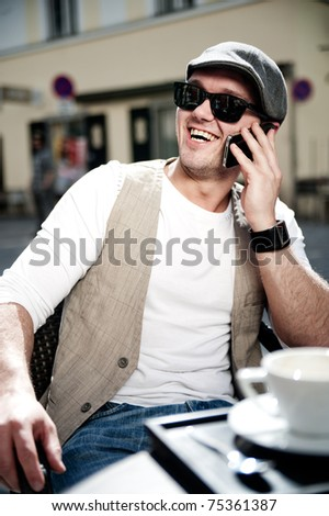 Cheerful man take a call with his smartphone