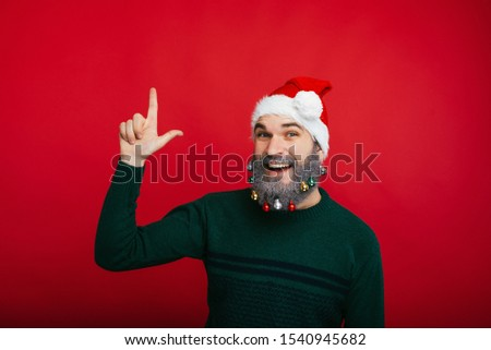 Cheerful man with decorated beard pointing up at copyspace over red background