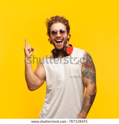 Cheerful man with headphones standing on yellow background and pointing up with index finger.