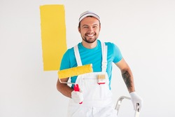 Cheerful man with paint roller standing on ladder and smiling for camera while coloring wall with yellow pigment during renovation works