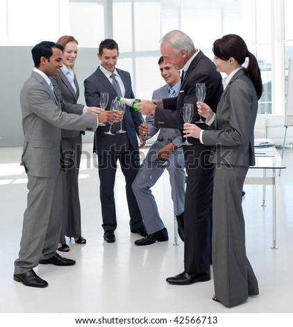 Cheerful manager serving Champagne to his team to celebrate a success