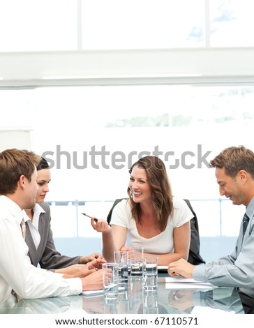 Cheerful manager talking to her team during a meeting in the office