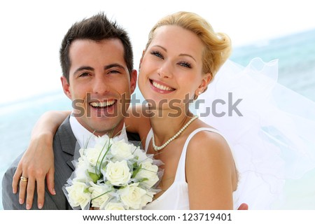 Cheerful married couple standing on the beach #123719401