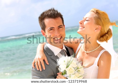 Cheerful married couple standing on the beach