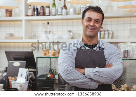Cheerful mature baker smiling, posing proudly at his bakery atore, copy space. Happy male confectioner wearing apron, welcoming you at his coffee shop. Friendly man working at his cafe