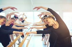 Cheerful mature ballerinas stretching with hands up standing at mirror in ballet class.