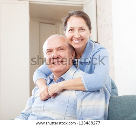 cheerful mature couple in home interior