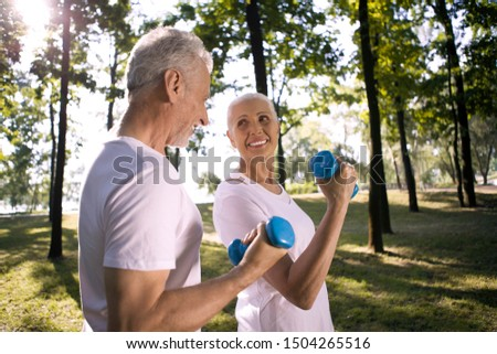 Cheerful mature lady looking at her husband while exercising outdoors #1504265516