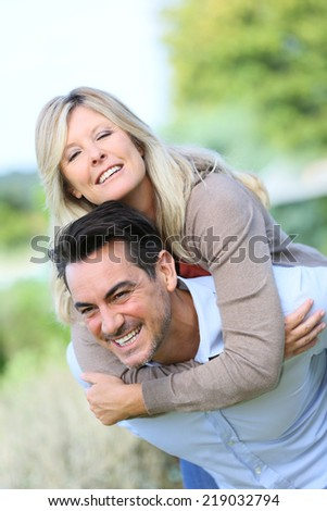 Cheerful mature man giving piggyback ride to woman #219032794