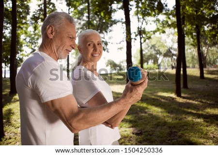 Cheerful mature man helping a smiling woman with hand weight training #1504250336