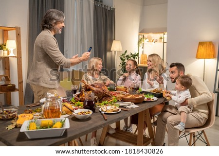 Cheerful mature man with smartphone taking photo of his big family on smartphone camera while standing in front of served festive table stock photo