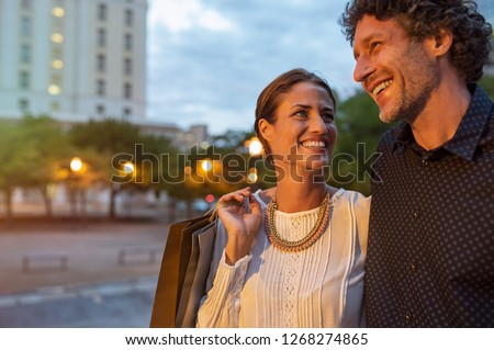 Cheerful mature woman carring shopping bags in evening with her boyfriend. Loving couple enjoying vacation while shopping in the city at dusk. Smiling husband and happy wife spending romantic time.