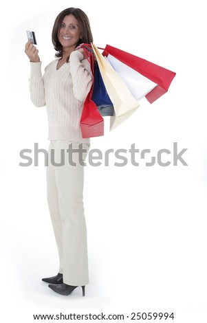 Cheerful mature woman holding shopping bags and credit card