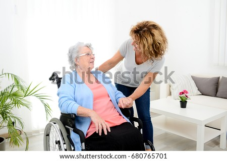 cheerful mature woman visiting retirement home residence with elderly senior woman on wheelchair