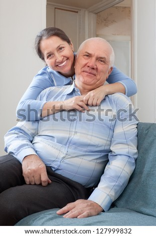 cheerful mature woman with smiling husband in home interior