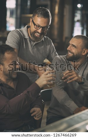 Cheerful men smiling, looking at each other and clinking crystal glasses. Friends having fun together, spending time in bar. Men communicating, drinking alcohol as brandy or whiskey.