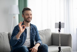 Cheerful middle-aged bearded man blogger broadcasting from home, using smartphone and tripod, copy space. Smiling male vlogger waving at mobile phone camera, shooting video for followers