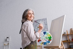 cheerful middle aged woman holding paintbrush and palette with colorful paints near blank canvas