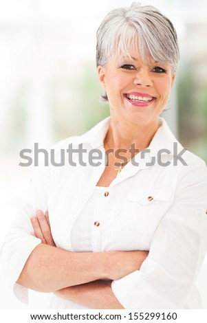 cheerful middle aged woman with arms folded