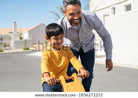 Cheerful middle eastern father helping excited son to ride wooden balance cycle on street. Happy boy enjoying riding bycicle with his dad. Dad teaching his indian son to ride bicycle outdoor.