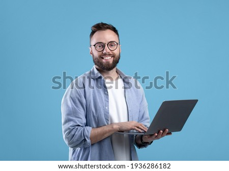 Cheerful millennial guy in glasses using laptop computer for online work or communication on blue studio background
