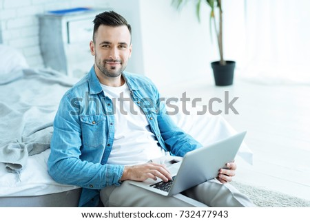 Cheerful millennial guy looking into camera while working