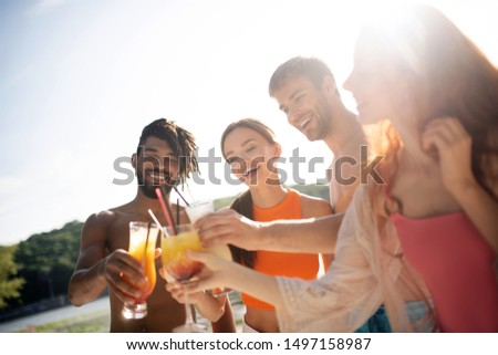 Cheerful millennials. Cheerful millennials laughing while drinking summer cocktails near river #1497158987