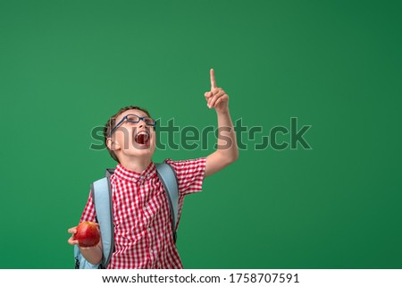 cheerful, mischievous boy holds an Apple in his hands, standing against the background of a green Board. an excited child directs attention up to the free space. Back to school. Photo stock ©