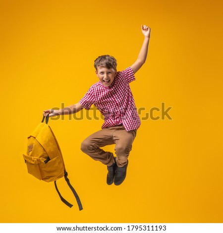 cheerful mischievous schoolboy in uniform with a backpack jumps on a yellow background. Dynamic images that go back to the school concept. beginning of holidays. Back to school. boy is ready to study. Photo stock ©