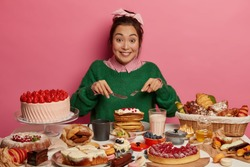 Cheerful mixed race woman eats with big appetite creamy pancakes, has unhealthy diet, looks gladfully, being sweet tooth, overeats desserts, isolated over pink background, cannot prevent obesity