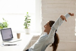 Cheerful mixed race woman sitting at workplace on chair bending stretching raising hands up, feels happy got a long-awaited post winning online lottery or accomplishing working day before vacation
