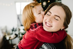 Cheerful mom kissing cute baby daughter girl near Christmas tree. Merry Christmas and Happy Holidays. Mother and little child having fun and playing together at home. Close up.