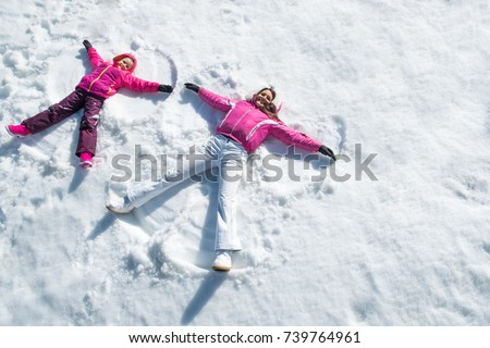Cheerful mother and daughter enjoying in snow while looking at camera. Happy woman with little child lying on snow making angel with arms and legs.Woman and smiling cute girl enjoying with copy space.