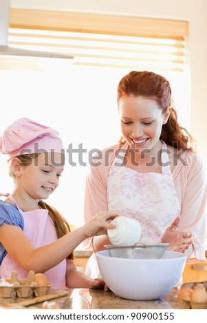 Cheerful mother and daughter preparing dough together - stock photo