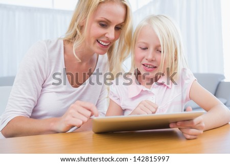 Cheerful mother and daughter using digital tablet in the living room